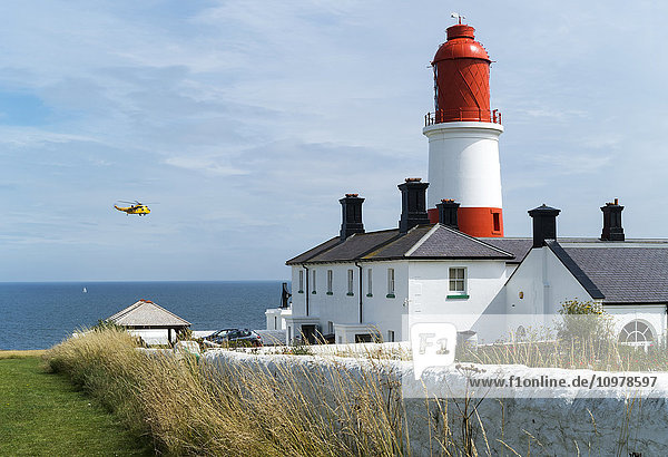 'A red and white lighthouse along the coast with a small yellow plane flying by; South Shields  Tyne and Wear  England'