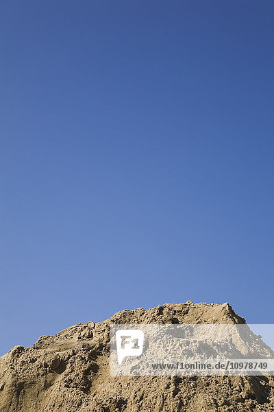 'Close-Up Of A Mound Of Fine Sand Against A Blue Sky; Laval  Quebec  Canada'