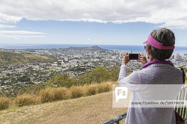 'Close up of a tourist taking a photo with a smart phone of downtown Honolulu and Diamond Head; Honolulu  Oahu  Hawaii  United States of America'