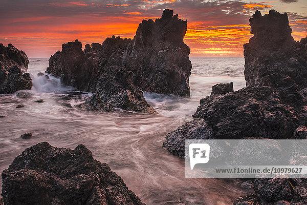 'The colours of sunrise behind coastal lava rocks; Laupahoehoe  Island of Hawaii  Hawaii  United States of America'