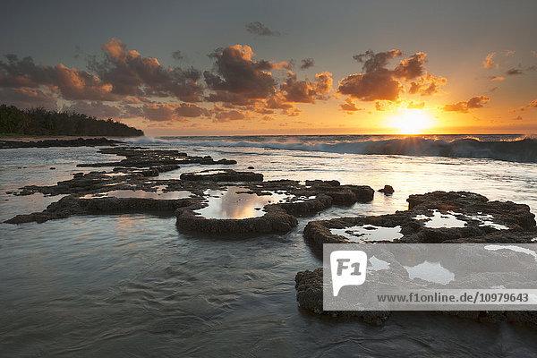 'Sunrise over surf and a lava reef; Kauai  Hawaii  United States of America'