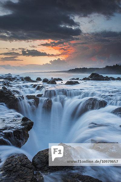 'Surf spills into a hole in a rock shelf along the coast in northeastern Kauai; Kauai  Hawaii  United States of America'
