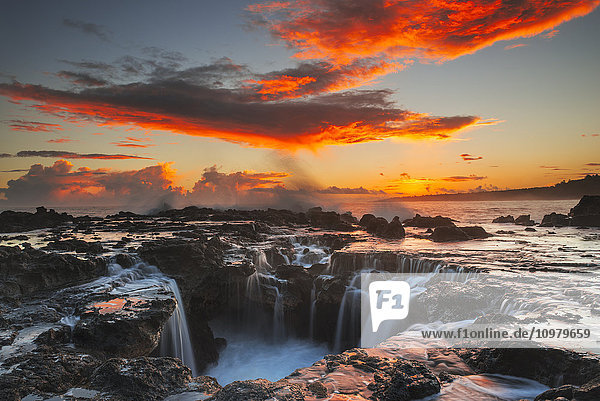 'Surf spills into a hole in a rock outcrop at sunrise on the east side of Kauai; Kauai  Hawaii  United States of America'