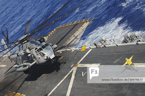 'A crewman onboard the USS Peleliu (LHA-5) guides a CH-53 Sea Stallion helicopter in for a landing; Hawaii  United States of America'