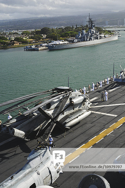 'Sailors and Marines ''man the rails'' in dress uniform as a ship passes by the USS Missouri (BB-63) in Pearl Harbor; Oahu  Hawaii  United States of America'