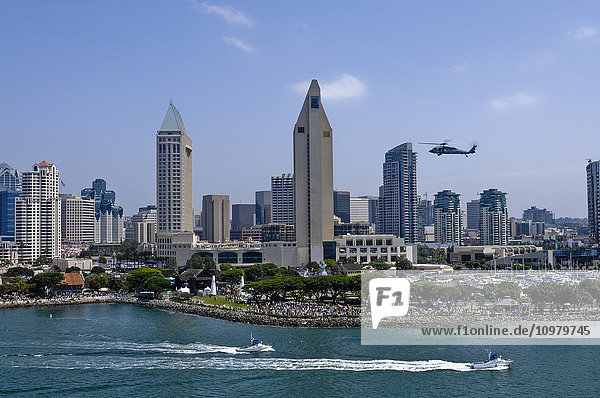 'A helicopter hovers as crowds gather at the shore in downtown San Diego; San Diego  California  United States of America'