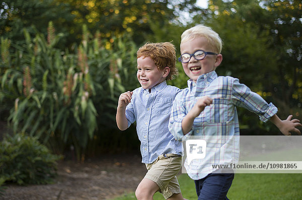 'Two young boys with big smiles running together on grass; Raleigh  North Carolina  United States of America'