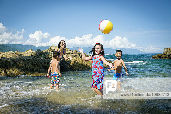 Mother and three children playing with beach ball