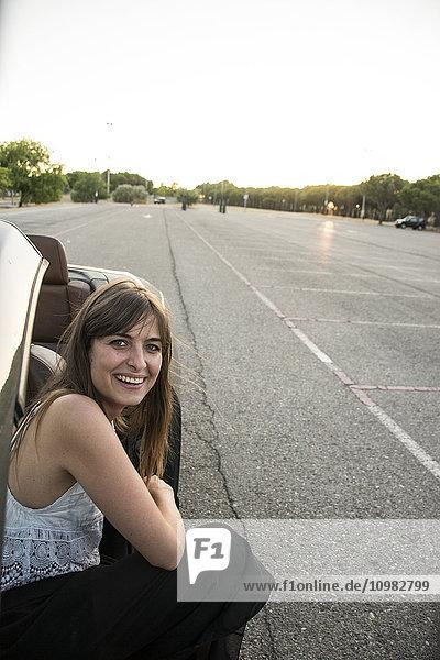 Lächelnde junge Frau kauernd neben dem Cabriolet