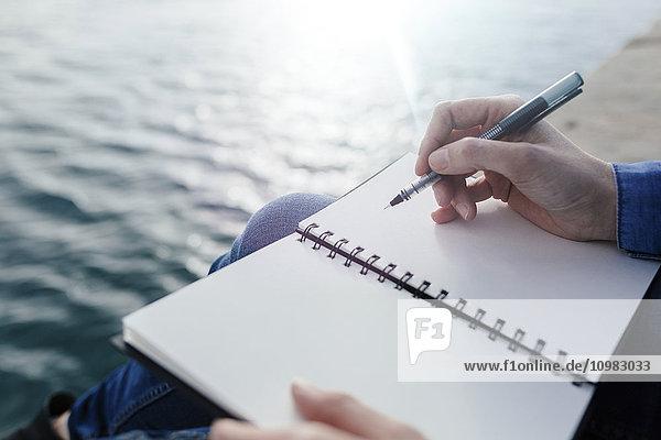 Junge Frau sitzt auf dem Dock und schreibt in einem Notizbuch.