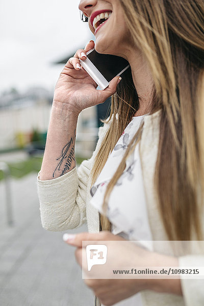 Glückliche Frau mit Tatoo im Arm auf dem Handy