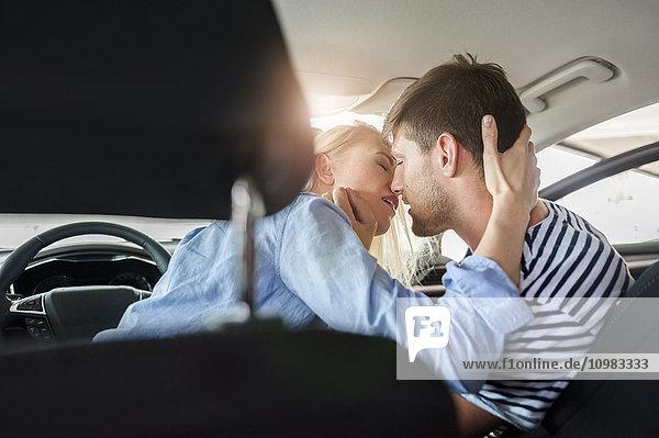 Verliebtes Paar  das sich in einem Auto küsst.