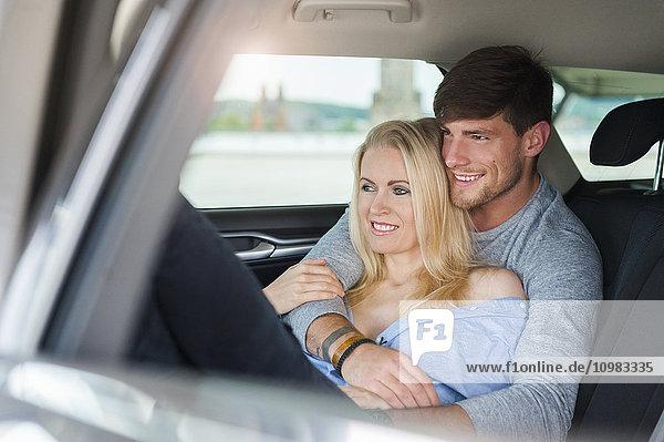 Lächelndes verliebtes Paar auf dem Rücksitz eines Autos