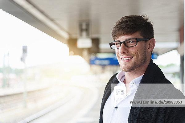 Lächelnder junger Mann am Bahnsteig