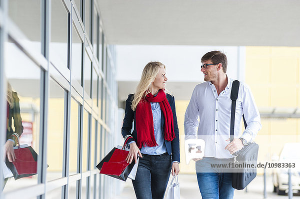 Smiling couple with bags passing urban building