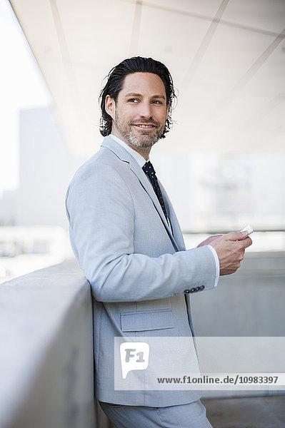Lächelnder Geschäftsmann mit Smartphone in der Ferne