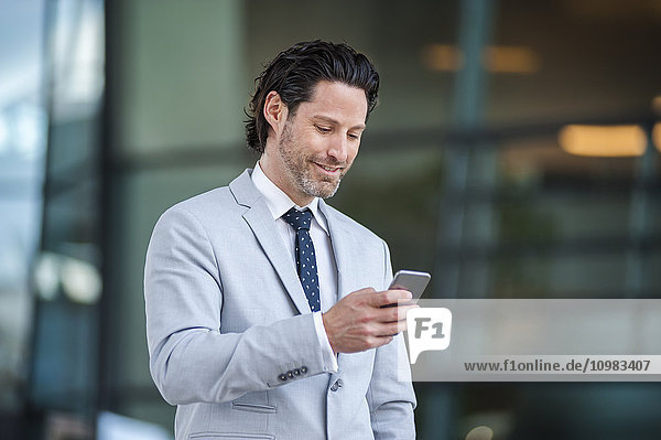Lächelnder Geschäftsmann beim Blick auf das Smartphone