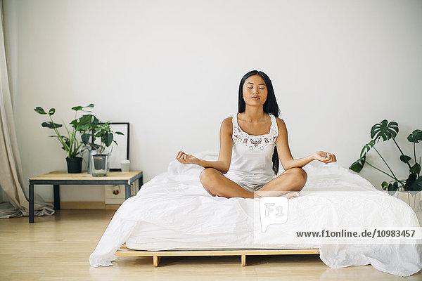 Junge Frau beim Yoga im Bett