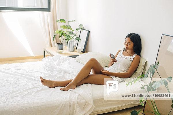 Junge Frau im Bett liegend mit dem Handy