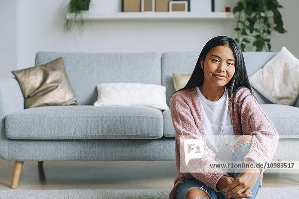 Porträt einer lächelnden jungen Frau  die zu Hause auf dem Boden sitzt.