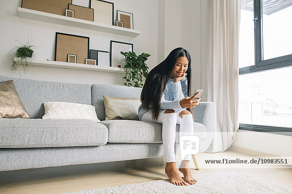 Junge Frau sitzt zu Hause auf der Couch und schaut auf das Smartphone.