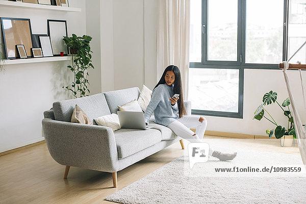 Junge Frau mit Smartphone sitzt zu Hause auf der Couch und schaut sich den Laptop an.