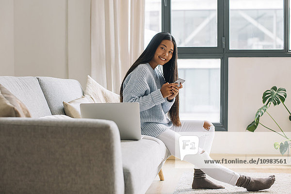 Smiling young woman sitting on couch with smartphone