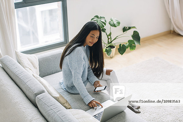 Junge Frau sitzt auf der Couch mit Smartphone und schaut auf den Laptop.
