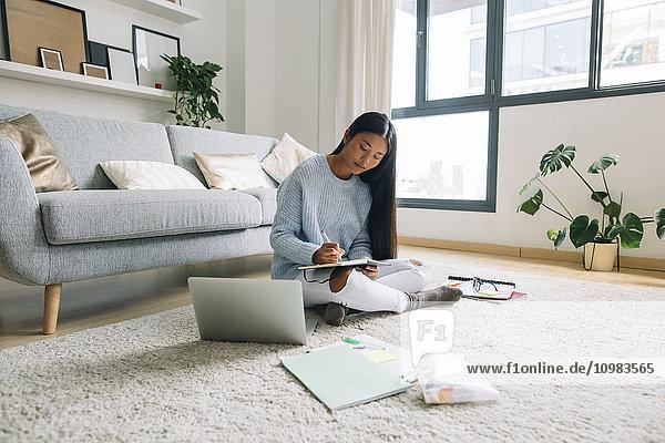 Junge Frau sitzt auf dem Boden im Wohnzimmer und schreibt etwas auf.