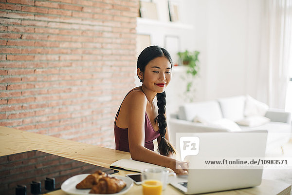Woman working with laptop on kitchen counter at home