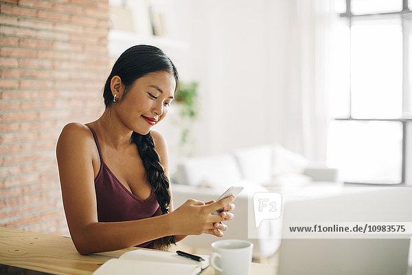 Lächelnde Frau schaut auf ihr Handy zu Hause