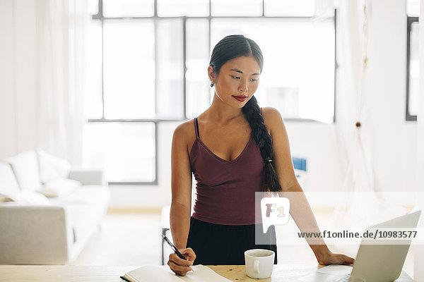 Frau bei der Arbeit mit dem Laptop zu Hause