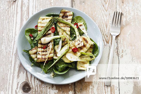 Salat mit Spinat  gegrillte Zucchini  Frühlingszwiebeln auf Teller  vegan