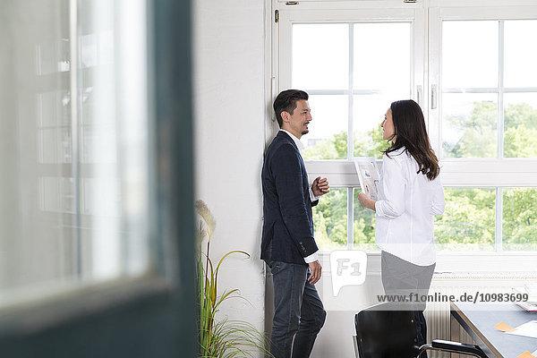 Geschäftsmann und Frau am Bürofenster stehend  diskutierend