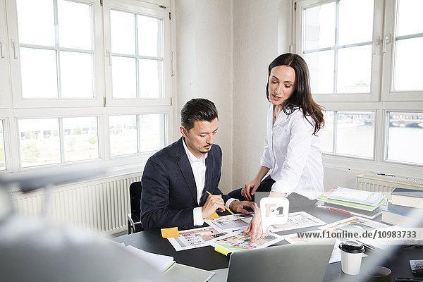 Geschäftsmann und Frau sitzen am Schreibtisch im Büro und arbeiten zusammen.