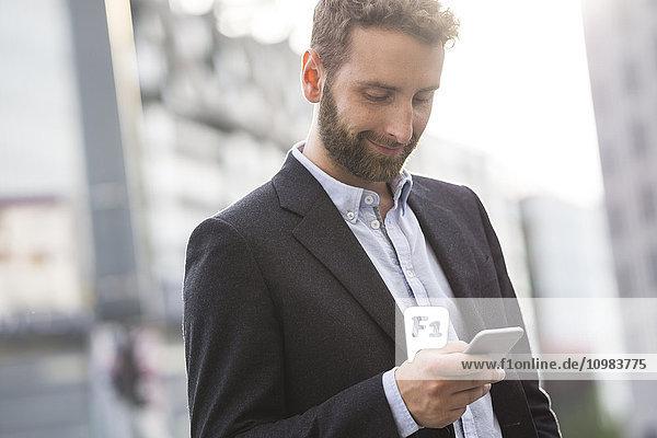 Lächelnder junger Geschäftsmann beim Blick auf das Handy im Freien