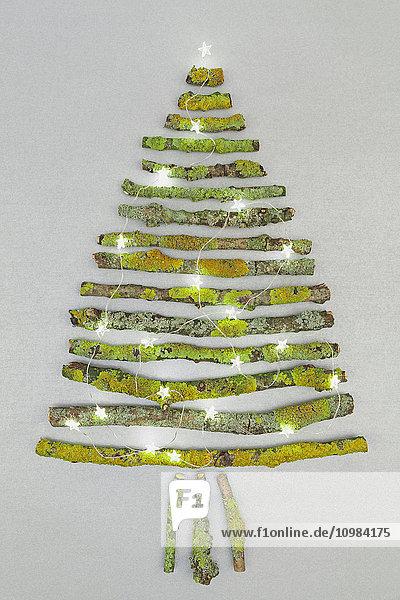 Weihnachtsbaum in Form von moosigen Ästen und Weihnachtsdekoration