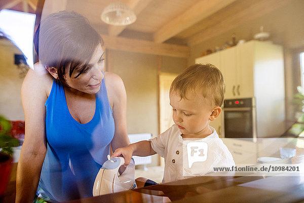Kleiner Junge hilft seiner schwangeren Mutter in der Küche mit elektrischem Schnurrbart