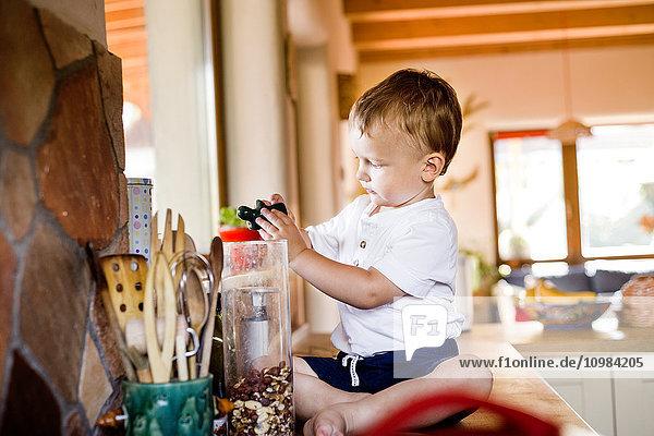 Der kleine Junge spielt in der Küche.
