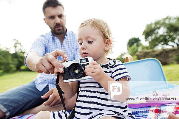 Vater zeigt seiner kleinen Tochter  wie man die Kamera benutzt.
