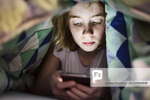 Mädchen liegt unter der Decke im Bett und schaut auf ihr Smartphone.