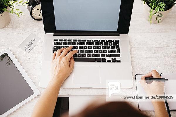 Frau am Schreibtisch mit Laptop  Draufsicht