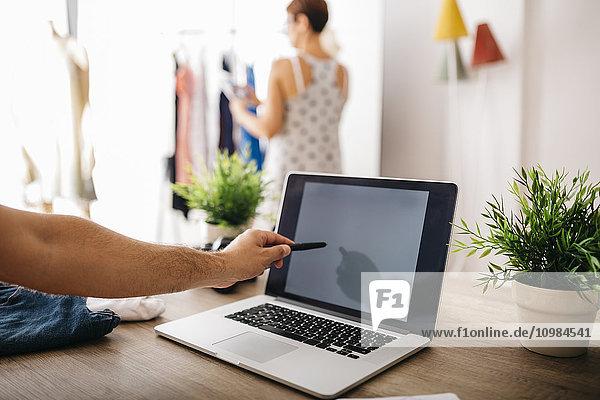 Mann zeigt auf Laptop mit Frau im Hintergrund
