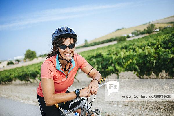 Spanien  Andalusien  Jerez de la Frontera  Portrait einer Radfahrerin  die lächelnd in die Kamera schaut.