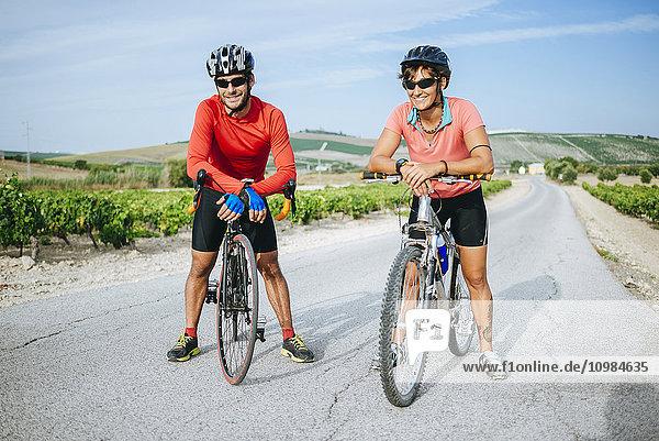 Spanien  Andalusien  Jerez de la Frontera  Paar  Radfahrer auf einer Landstraße zwischen Weinbergen