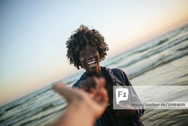 Junge Frau nimmt bei Sonnenuntergang die Hand eines Mannes am Strand.