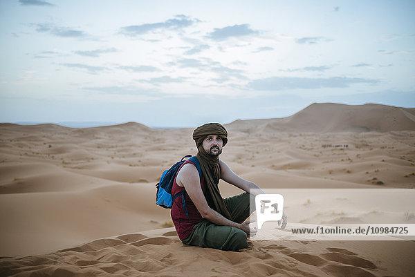 Tourist mit Turban in der Wüste sitzend