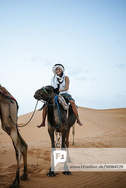 Frau mit Turban auf einem Kamel in der Wüste