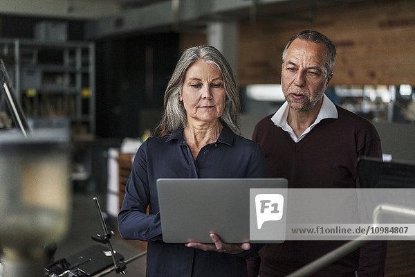 Senior Frau und Mann in einer Druckerei mit Blick auf Laptop