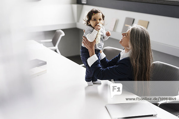 Senior businessswoman in conference room holding baby girl